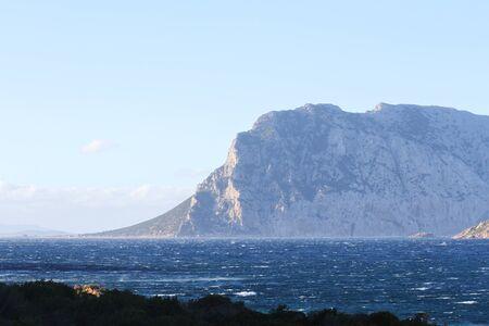 Paradise landscape view with Mountain overlooking the blue sea - Mediterranean italian scrub next wild nature sea - Sardinia Island - Vacation concept and wanderlust - Focus on horizon - Light filter Standard-Bild