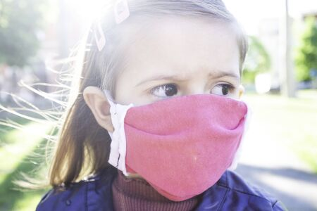 Little caucasian girl wearing medical handmade face mask protect for fine dust and as protection new coronavirus - Little girl with big afraid eyes wearing pink face mask protective outdoors