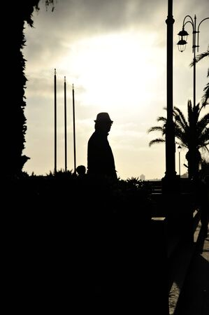 Silhouette of a man in a coat and hat on sea coast at sunset. Mystery or solitude concept. Suitable for a cover of a thriller book. Copy space for text. Foto de archivo - 150128228