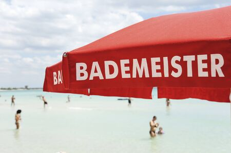 Red lifeguard umbrella on a beach against blue sky. Some bathers ont he background. The text on the umbrella Bademeister translates as Lifeguard, for german bathers. Risk and rescue concept. Tyrrhenian  sea, South Italy. Archivio Fotografico