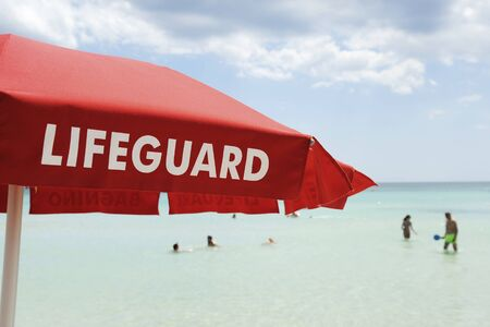 Red lifeguard umbrella on a beach against blue sky. Some bathers ont he background. Risk and rescue concept. Tyrrhenian  sea, South Italy.