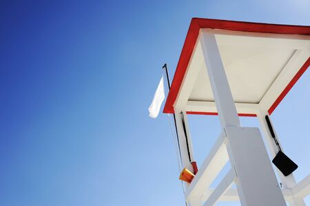 Lifeguard wooden tower on the beach against blue sky. Megaphone and other tools hang from the tower. The white flag waving on the roof.Copy space for text. Risk and rescue concept.