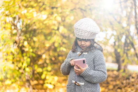 Cute little girl holding smartphone at park during foliage time - Little girl using a phone typing and taking photos of yellow autumnal landscape - Childhood and tech concept in the nature, Copy space 免版税图像