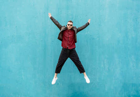Cool man in casual indie clothes jumping outdoor with open arms against a blue wall background - Trendy guy having fun dancing and celebrating outside - Lifestyle concept for joyful mature men
