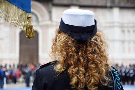 Back view of policewoman wearing uniform during the military demonstration or parade - Detail with uniformed woman standing for the military ceremony in the city - Concept of women's empowerment