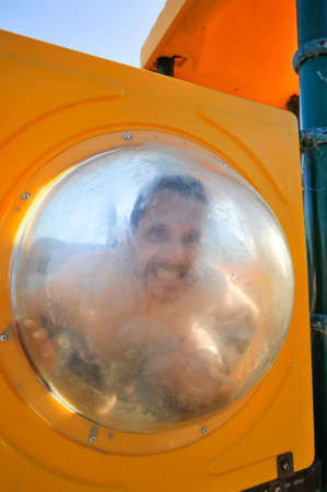 A man makes funny faces behind the clear plastic porthole in the kids' gym on the beach during summer vacation - Guy enjoying life on the beach making comic faces - Forever young concept