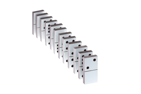 white dominoes standing in a row on a white background Stock Photo