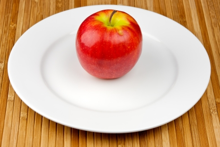 apple on a plate standing on a bamboo napkin