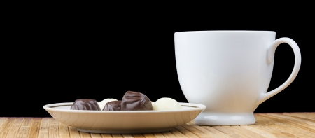 cup and saucer sweet candy isolated on black background photo