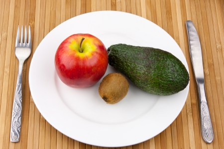 ripen: kiwi, avocado and apple on a white bowl with cutlery Stock Photo