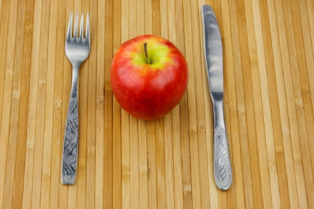 chomp: red apple lying on a bamboo napkin with cutlery