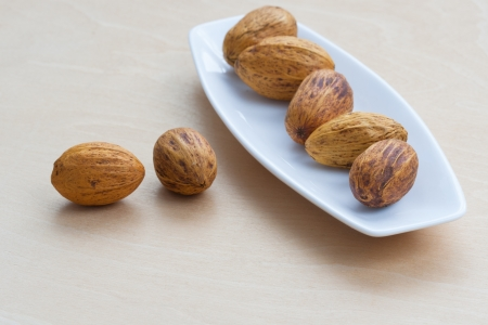 brown nuts lying in a row on a platter Stock Photo - 16864487