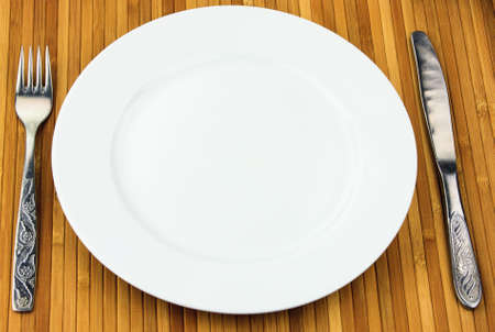 white plate, knife and fork at bamboo napkin photo