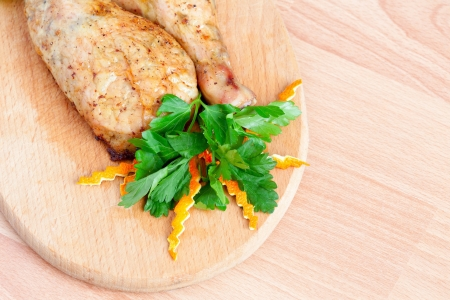 Fried chicken legs with parsley on the board photo