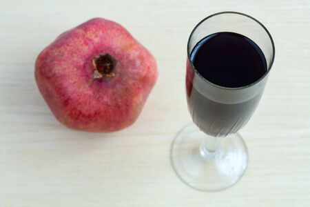 Goblet of wine and a pomegranate on the table