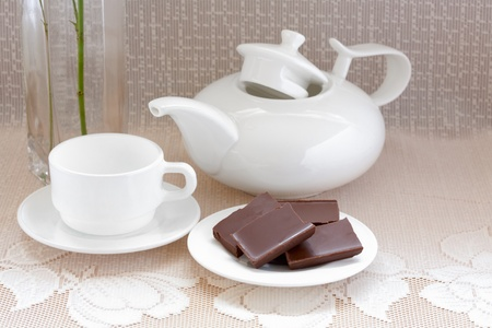 teapot, cup and chocolate on a plate photo
