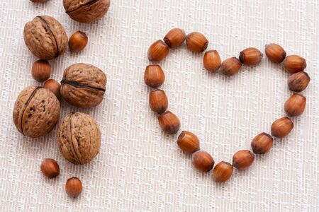 walnuts, hazelnuts on a wooden background in the form of heart photo