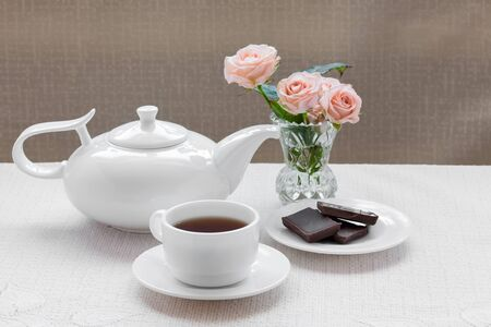 cream tea: teapot, cup, roses, and chocolate on a plate