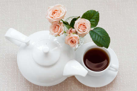 teapot, cup, and  roses on a plate photo