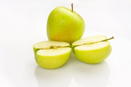 whole and sliced apple with reflection