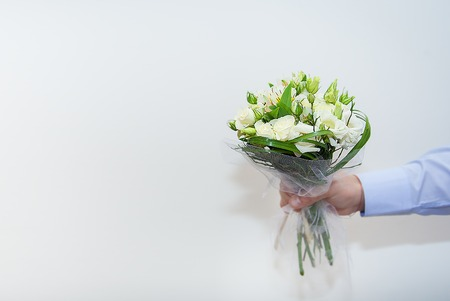 wedding bouquet in a hand of the groom on white background. Stock Photo