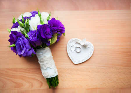 bridal bouquet of roses, peony and rings on a saucer in the form of heart. Stock Photo