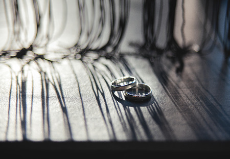 Wedding rings on a wooden board, with long shadows from drapery.