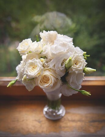 Beautiful white Roses in a glass vase near window Stock Photo