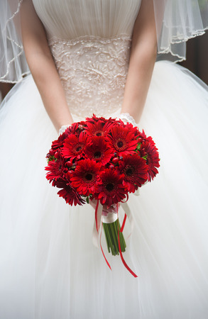 Wedding bouquet in hands of the bride. Red chrysanthemums