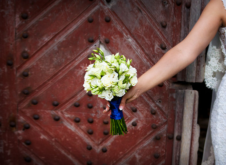 wedlock: Bride holding beautiful wedding flowers bouquet on old wooden background