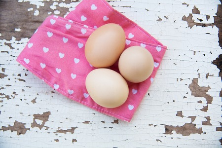cracky: Eggs on pink tablecloth over old cracky white wooden background. Top view Stock Photo