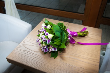Purple irises bouquet over wooden table