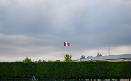 Flag of France against the sky and green bushes
