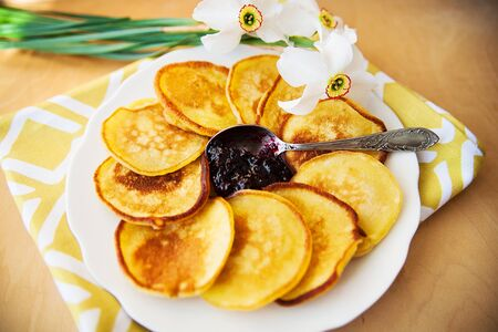 Pancakes with jam and spoon on a plate and white daffodils on wooden background. Top view