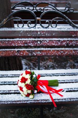 Wedding bouquet on a winter park bench.