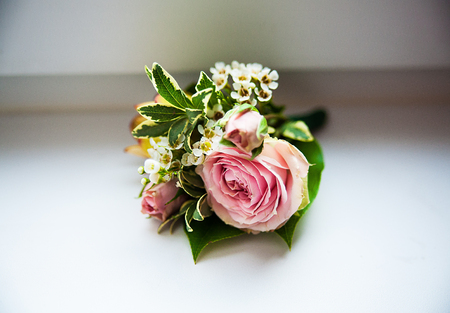 boutonniere: Grooms boutonniere closeup. Wedding boutonniere of roses.
