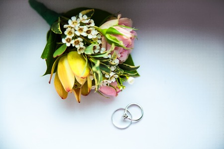 rings and flowers. Grooms boutonniere closeup. Wedding boutonniere of roses.