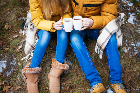 red cardigan: coffee mugs iron in the hands of lovers. life style Stock Photo