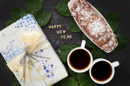 plaything: inscription of new year on a black board with a gift, muffins and coffee