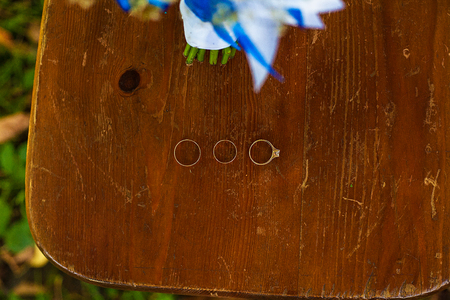 Three wedding rings on a wooden floor