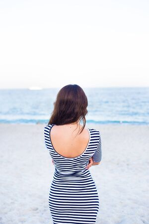 girl in a striped dress on the beach is back