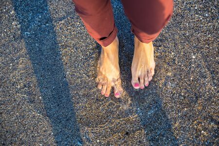 painted toenails: Woman standing on the beach with wave sea, Top view.