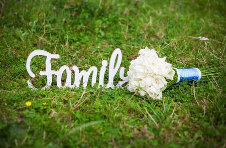 family wooden letters and a beautiful wedding bouquet Stock Photo