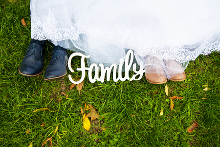 wooden letters family and bridal legs on the grass