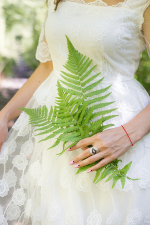 girl in a white dress, holding a green fern leaves in the forest Stock Photo
