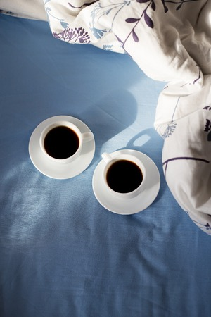 Two white cups of coffee are in bed, sunny morning
