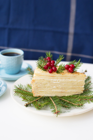 cake decorated Christmas tree branches and berries on a background of the Christmas tree and two cups of coffee Stock Photo