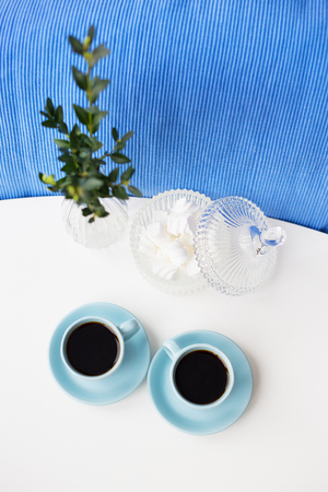 Two blue coffee cup on the table with a vase and saucer with marshmallows