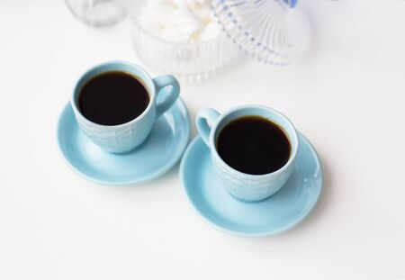 Two blue coffee cup on the table and saucer with marshmallows