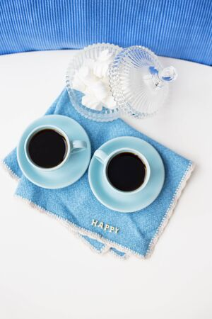 Two blue coffee cups on blue napkin saucer Marshmallow